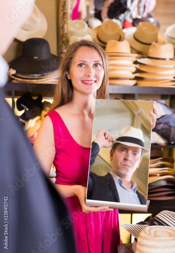 222fd17b woman holding mirror and showing customer his reflection in hats shop