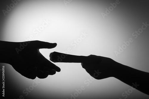 Fotografía  dark economy. Two hands with money