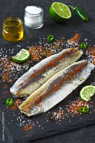 Herring fillet with sea salt and spices on a gray stone board