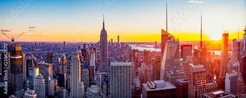 New York City / Manhattan skyline panorama with urban skyscrapers at sunset, USA.