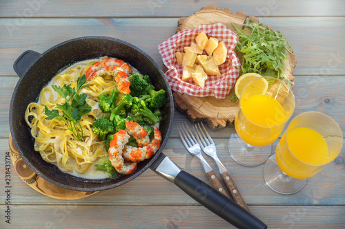 Fotografía  Whole grain pasta with shrimps and cheese on wooden table, top view