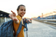 portrait of a young woman traveler with small backpack on the railway stantion