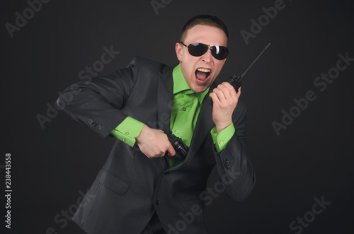 Fotografía  Security agent man in suit and sunglasses pull out a gun and is asking for assistance on the radio station isolated on black background