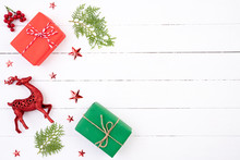 Christmas Background Concept. Top View Of Christmas Green And Red Gift Box With Spruce Branches, Pine Cones, Red Berries, Star And Reindeer On White Wooden Background.