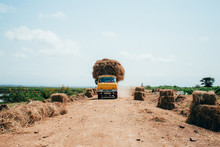 Van Driving Down A Road Carrying Hay
