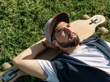 Young Man With Skateboard Lying On Grass And Listening To Music
