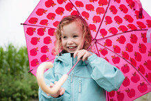 Happy Cute Girl Carrying Pink Umbrella While Standing Outdoors During Rainy Season