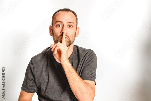 Man in studio asking for silence with a wave of his hand putting a finger on his lips, model expressions isolating white background