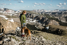 Male Hiker With Dogs Standing On Mountain Against Cloudy Sky