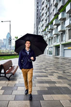 Full Length Of Young Businessman With Umbrella Walking On Footpath In City During Rainfall