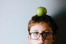 Close-up Portrait Of Boy Carrying Granny Smith Apple On Head Against Wall At Home