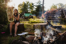 Girl Playing Tuba While Sitting On Tree Stump In Forest