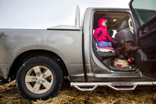 Side View Of Girl With Calf Sitting In Pick-up Truck At Farm