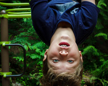 Close-up Portrait Of Cute Boy Hanging Upside Down Against Trees At Park