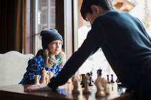 Siblings Playing Chess At Home