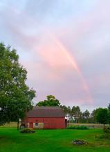 Rainbow Over Barn Against Cloudy Sky During Sunset
