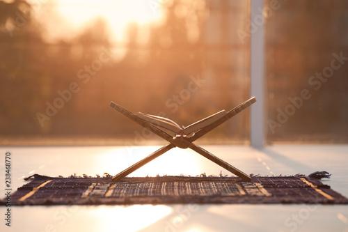Rehal with open Quran on Muslim prayer mat indoors