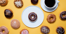 Overhead View Of Variety Of Donuts With Coffee Cup