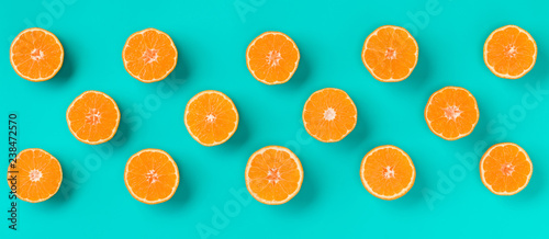 Foto op Canvas Vruchten Fruit pattern of fresh mandarin slices on blue background. Flat lay, top view. Pop art design, creative summer concept. Half of citrus in minimal style. Tangerine.