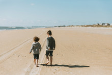 Rear View Of Brothers Walking On Beach