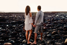 Rear View Of Couple Looking At Sea While Standing On Rocks Against Clear Sky During Sunset