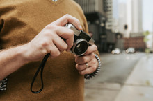 Midsection Of Man Holding Camera While Standing On City Street