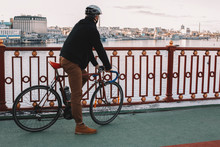 Side View Of Male Cyclist With Bicycle Standing On Bridge Over River Against Sky In City