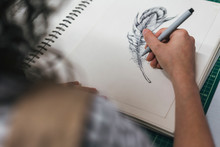Cropped Image Of Female Artisan Drawing On Book In Workshop