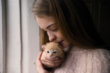 Close Up Of Woman Kissing Kitten By Window At Home