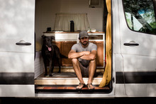 Thoughtful Man Sitting By Dog In Motorhome