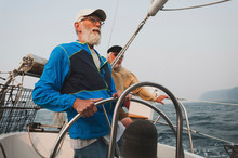 Senior Man With Male Friend Sailing Boat On Sea Against Clear Sky