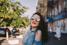 Smiling Young Woman Wearing Sunglasses While Standing In City