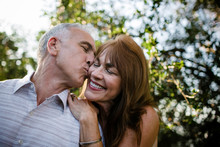 Mature Couple Kissing In Park