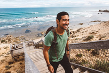 Smiling Hiker With Backpack Climbing Wooden Steps At Beach Against Sea