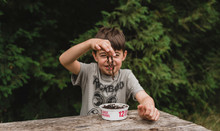Boy Holding Earthworm At Wooden Table While Sitting Against Trees In Forest