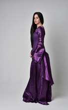 Full Length Portrait Of Beautiful Girl With Long Black Hair,   Wearing Purple Fantasy Medieval Gown. Standing Pose On Grey Studio Background.