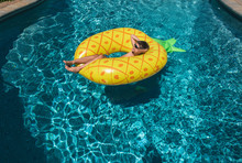 High Angle View Of Shirtless Boy Relaxing On Inflatable Ring In Swimming Pool