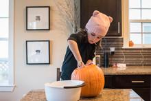 Girl Making Jack O' Lantern At Home During Halloween
