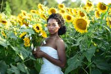 Portrait Of Bride With Flower Bouquet Standing On Sunflower Farm