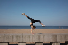 Young Woman Exercising On Retaining Wall