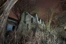 Abandoned Wooden Building By Bare Trees In Forest At Night