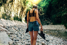 Rear View Of Woman Holding Sandals While Walking On Rocks In Forest