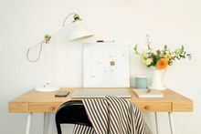 Technologies With Calendar And Desk Lamp By Flower Vase On Table Against Wall In Office