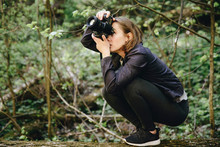 Side View Of Woman Photographing With Digital Camera While Crouching In Forest
