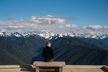 Rear View Of Man Sitting On Bench And Looking At Snowcapped Mountains At Olympic National Park