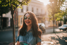 Cheerful Young Woman Wearing Sunglasses While Standing On Sidewalk In City During Sunny Day