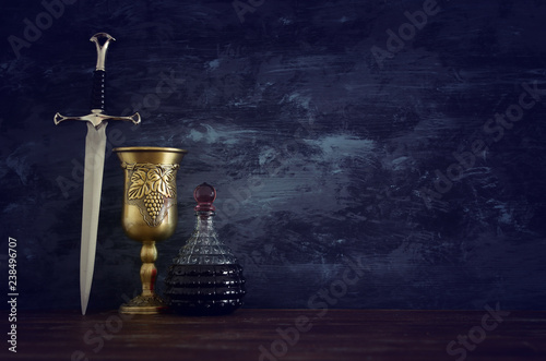 low key image of wine cup and sword. fantasy medieval period. Tablou Canvas