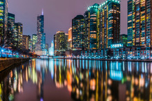 Illuminated Modern Buildings Reflecting On Calm Chicago River Against Sky At Night