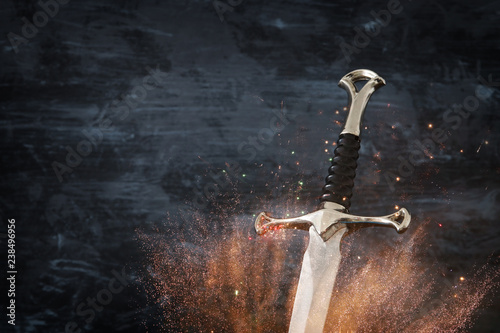 low key image of silver sword with fire sparks Fototapet