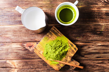 Top View Of A Cup Of Matcha Tea With Milk Jug.